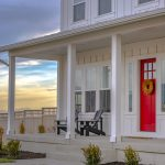 front porch with a bright red front door
